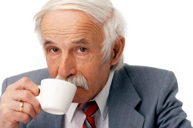 Retrato de un hombre de negocios mayor tomando café sobre blanco.