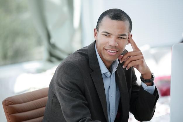 Retrato de hombre de negocios pensativo sentado detrás de un escritorio.