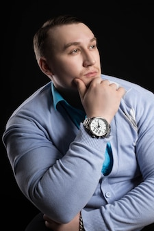 Retrato de un hombre de negocios pesista con gran músculo en la camisa azul y chaqueta de punto sobre un fondo negro. entrenador de fitness hombre atlético en power athletics