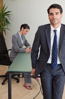 Retrato de un hombre de negocios posando mientras su colega está trabajando