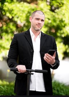 Retrato de hombre de negocios posando con scooter