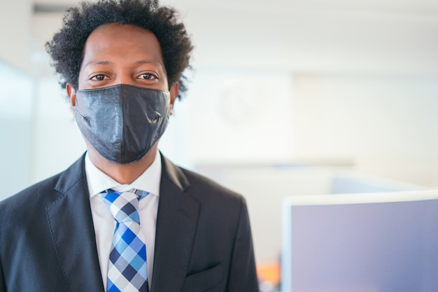 Retrato de hombre de negocios profesional con mascarilla mientras está de pie en la oficina moderna. nuevo estilo de vida normal. concepto de negocio.