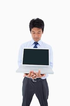 Retrato de un hombre de negocios que muestra una computadora portátil