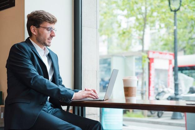 Retrato de un hombre de negocios que usa el ordenador portátil con la taza de café para llevar en la tabla en café
