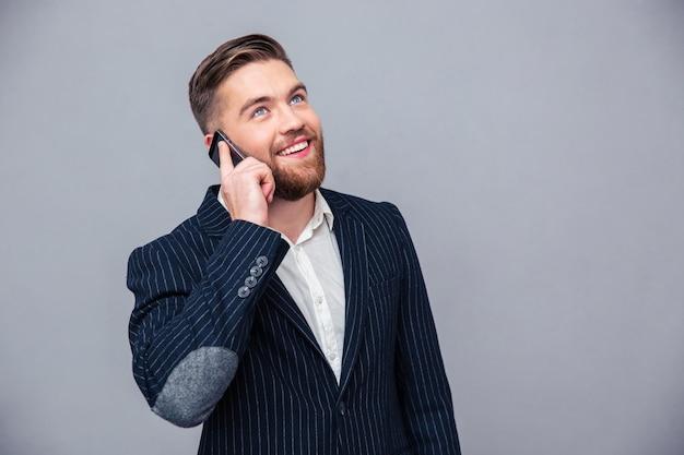 Retrato de un hombre de negocios reflexivo feliz hablando por teléfono y mirando hacia arriba sobre la pared gris