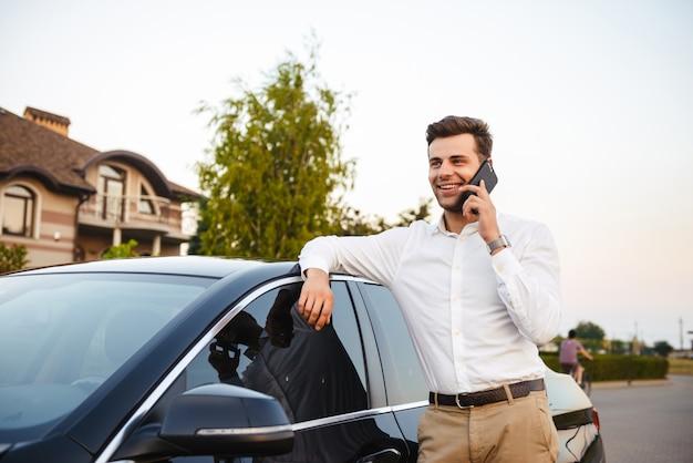 Retrato de hombre de negocios rico vistiendo traje, de pie cerca de su automóvil negro de lujo y hablando por teléfono inteligente