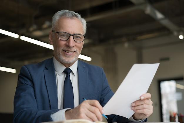 Retrato de hombre de negocios senior guapo sosteniendo documentos trabajando en office