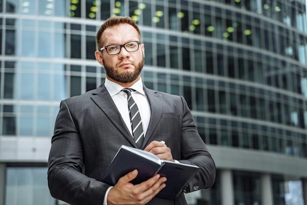 Retrato de un hombre de negocios serio en un traje y gafas en la ciudad.