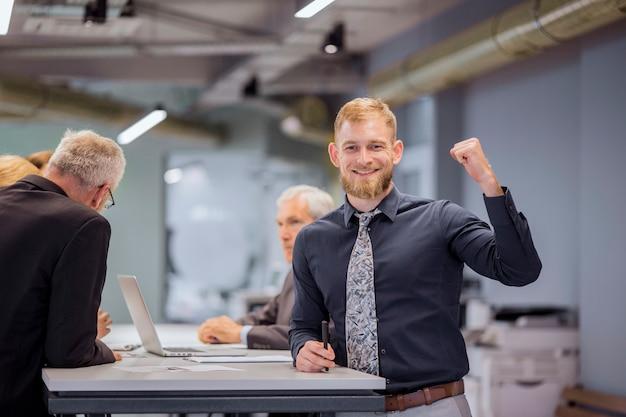 Retrato de hombre de negocios sonriente apretando su puño mientras el equipo discutiendo en el fondo