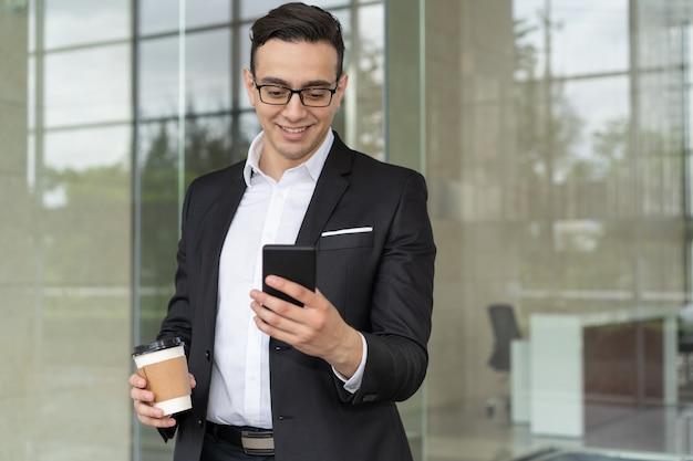 Retrato de hombre de negocios sonriente con mensaje de lectura de café