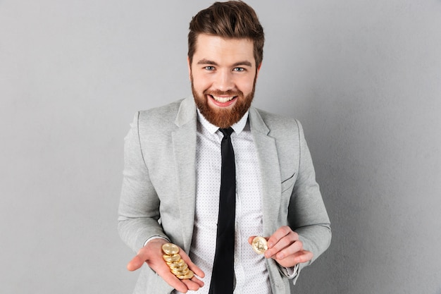 Retrato de un hombre de negocios sonriente mostrando bitcoins dorados