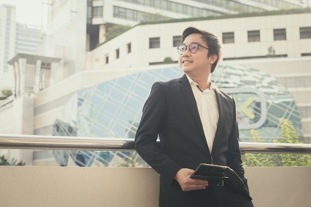 El retrato del hombre de negocios sonriente parece confiado usando la tableta de la computadora