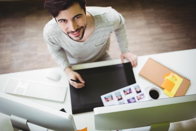 Retrato de hombre de negocios con tableta gráfica en la oficina