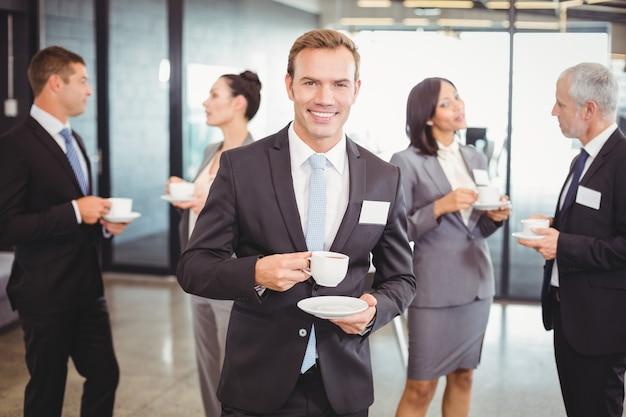 Retrato de hombre de negocios tomando té durante el recreo