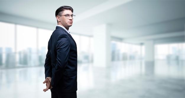 Retrato de un hombre de negocios con traje. el esta parado en la oficina de un rascacielos