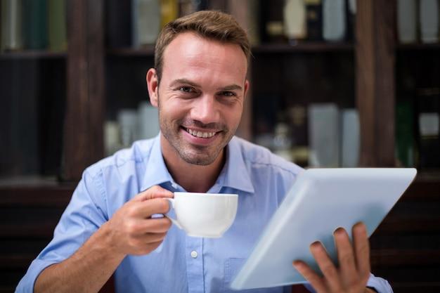 Retrato de hombre de negocios usando tableta digital mientras toma un café