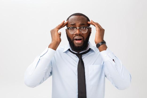Retrato de un hombre negro desesperado y molesto que grita de rabia y rabia arrancando su cabello