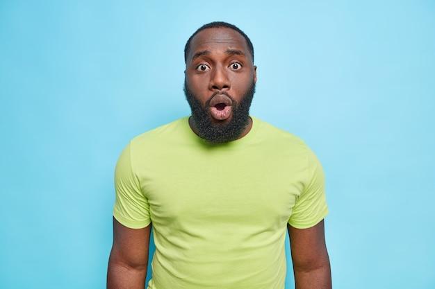 El retrato del hombre parece avergonzado al frente tiene una expresión de asombro que mantiene la boca abierta viste una camiseta verde informal aislada sobre una pared azul