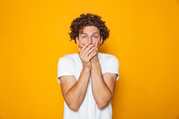 Retrato de un hombre de pelo rizado sorprendido cubriendo la boca