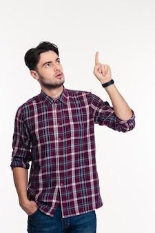 Retrato de un hombre pensativo apuntando con el dedo hacia arriba aislado en una pared blanca