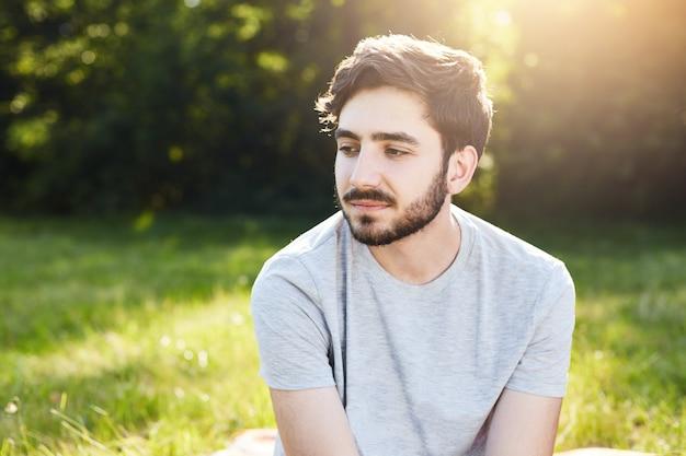 Retrato de hombre pensativo con barba y elegante peinado mirando hacia abajo con sus encantadores grandes ojos oscuros pensando en su vida disfrutando de la quietud