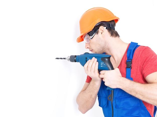 Retrato de un hombre perforando un agujero en la pared.