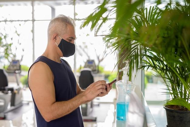 Retrato de hombre persa maduro con máscara para protegerse del brote del virus corona distanciamiento social en el gimnasio