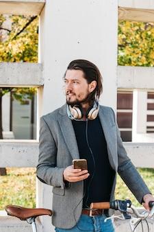 Retrato de un hombre de pie cerca de la pared con bicicleta sosteniendo teléfono móvil