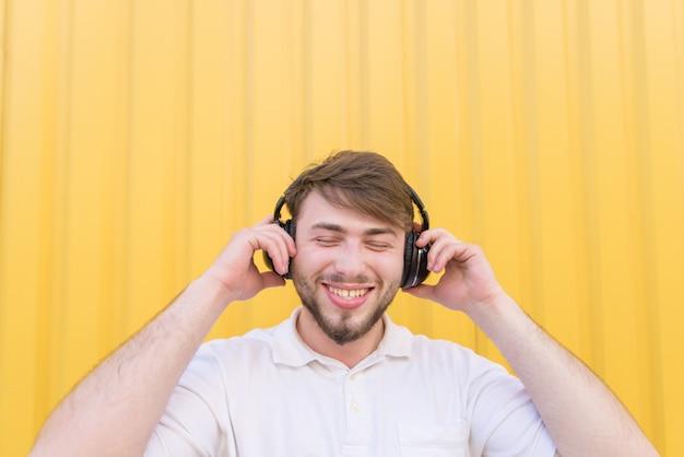 Retrato de un hombre de pie en una pared amarilla con un teléfono en sus manos y auriculares en la cabeza.