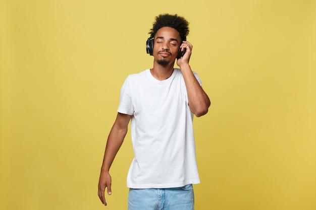 Retrato de un hombre de piel oscura con los ojos cerrados, tiene auriculares, escucha su música favorita.