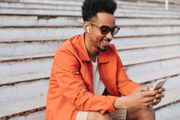 Retrato de hombre de piel oscura rizado en chaqueta naranja y gafas de sol sonriendo sinceramente y sosteniendo el teléfono