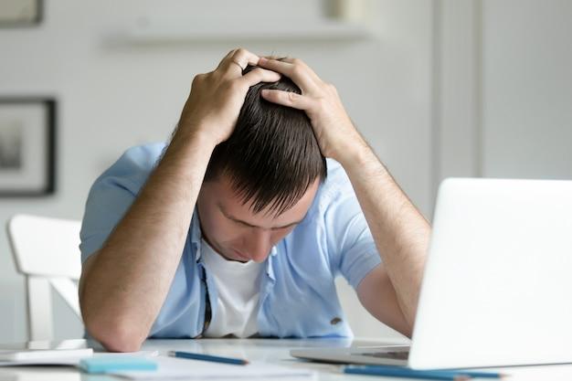 Retrato del hombre que agarra su cabeza en la desesperación cerca de la computadora portátil