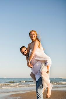 Retrato de un hombre que da transporte por ferrocarril a su esposa alegre en la playa contra el cielo azul claro