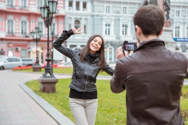 Retrato de un hombre que hace la foto de la mujer que ríe al aire libre en la vieja ciudad europea