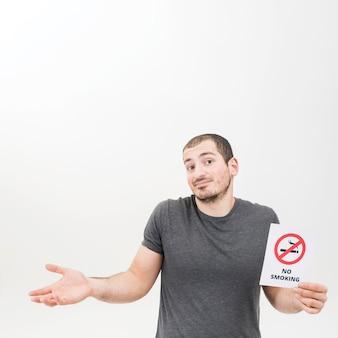 Retrato de un hombre que lleva a cabo la muestra de no fumadores que se encoge de hombros contra el fondo blanco
