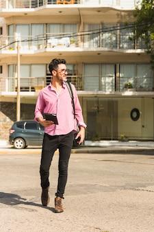 Retrato de un hombre que sostiene el diario en la mano caminando en la calle con su mochila