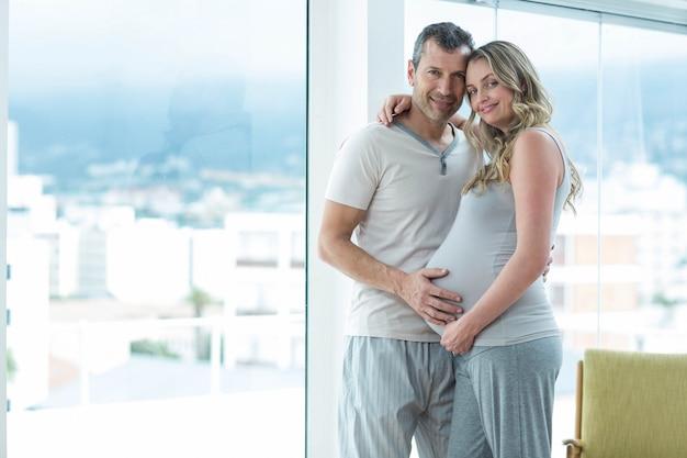 Retrato del hombre que sostiene el estómago de la mujer embarazada en dormitorio