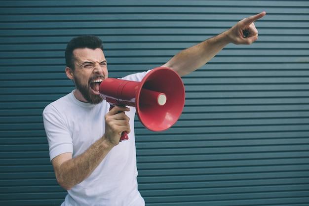 Retrato del hombre que sostiene el megáfono rojo disponible nad que grita en él. también el chico está apuntando hacia arriba con el dedo. aislado en rayas