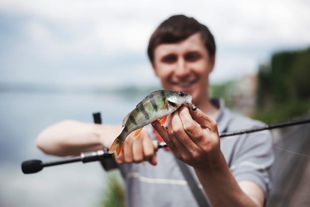 Retrato del hombre que sostiene pescados cogidos en el gancho