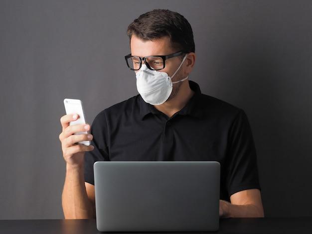 Retrato de un hombre que trabaja en casa con ordenador portátil y teléfono con máscara protectora en su rostro. conciencia de la enfermedad por coronavirus (covid19). la gente protege de covid-19 o 2019 ncov.