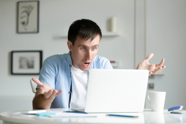 Retrato de un hombre que trabaja en el escritorio con la computadora portátil