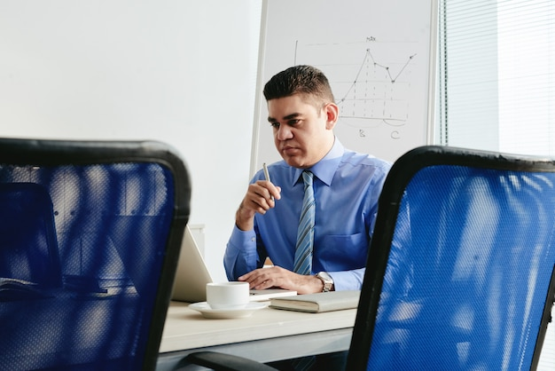 Retrato de hombre que trabaja en la oficina en la computadora portátil
