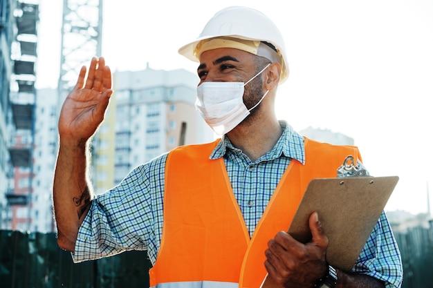Retrato de hombre de raza mixta constructor en ropa de trabajo y casco con máscara médica de cerca