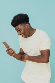 Retrato de hombre riendo mirando smartphone