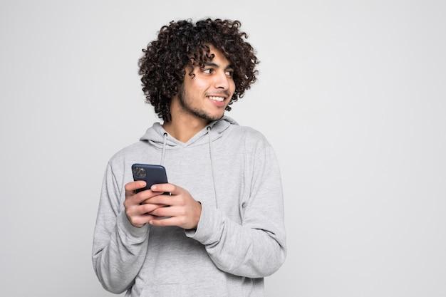 Retrato del hombre rizado hermoso que sostiene el teléfono aislado en la pared blanca