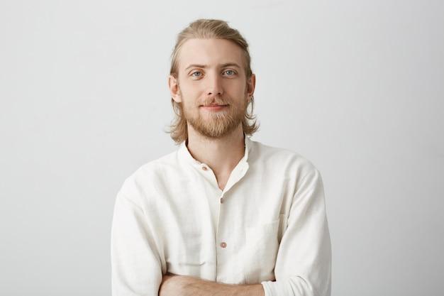 Retrato de hombre rubio guapo positivo con barba y bigote, de pie con las manos cruzadas en camisa blanca con leve sonrisa y expresión de confianza