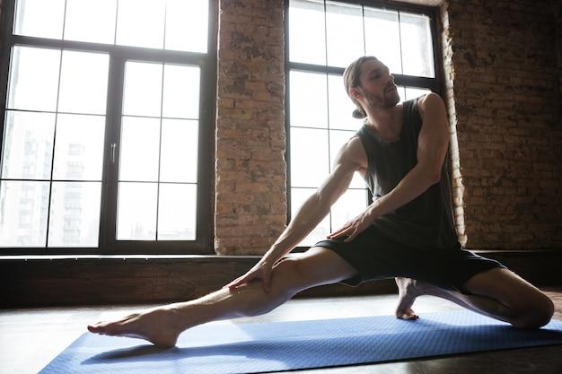 Retrato de un hombre sano estirando la pierna antes del entrenamiento de gimnasio