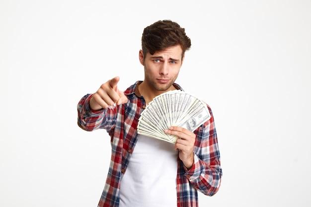 Retrato de un hombre seguro serio con un montón de dinero