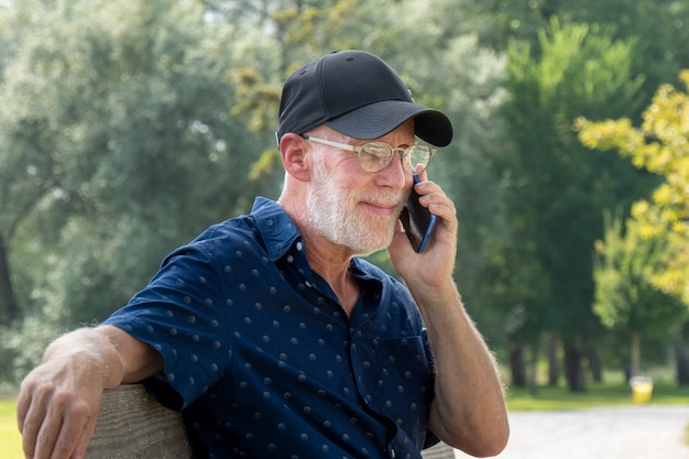 Retrato de hombre senior con barba y gafas con smartphone