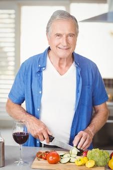 Retrato de hombre senior cortar verduras